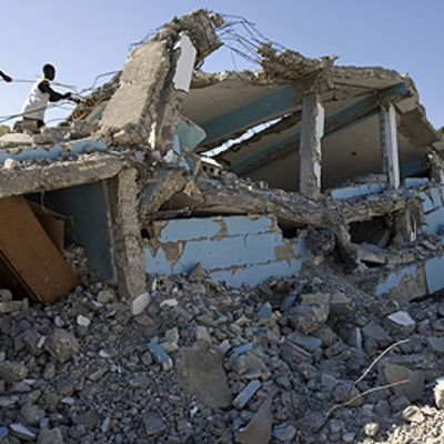 Miehiä kiipeilee sortuneen koulurakennuksen päällä.