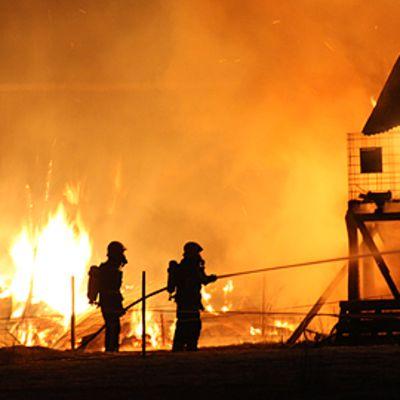 Kaksi palomiestä ruiskuttaa vettä navettaan yöllä.