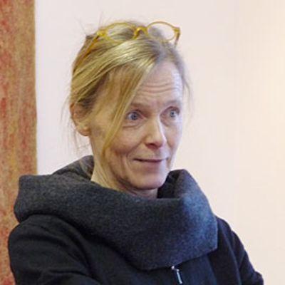 Kuvassa tekstiilitaiteilija Nina Nisonen työnsä vieressä