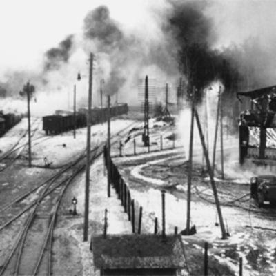 Vaasan rautatieaseman ratapihalla junan vaunut ja radan läheisyydessä olevat rakennukset palavat.