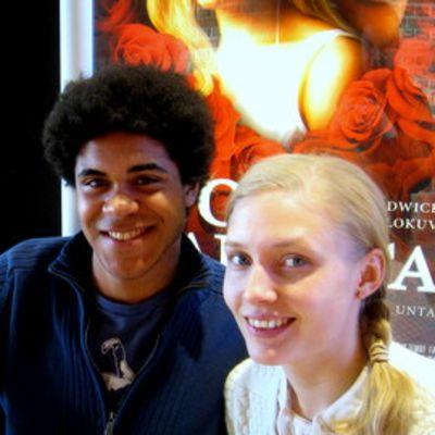 Tumma mies ja vaalea nainen elokuvajulisteiden edessä