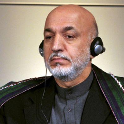 Hamid Karzai kuuntelee kuulokkeilla lehdistötilaisuudessa.