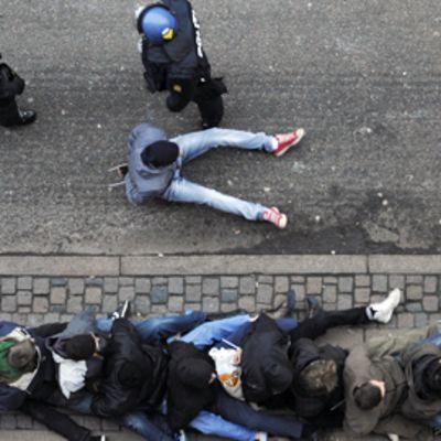 Mielenosoittajia istuu kadulla Kööpenhaminassa.