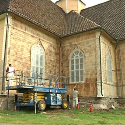 Kaksi miestä poistamassa maalia Lohtajan kirkon ulkoseinästä kirkon kunnostustöiden yhteydessä.