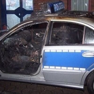 Saksalainen poliisiauto öisellä kadulla. Auton ovi auki. Auton ohjaamo palanut.