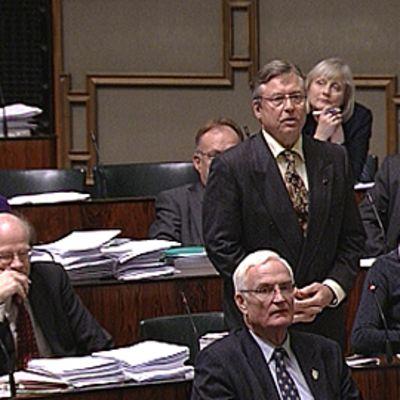 Eduskunnan ulkoasiainvaliokunnan puheenjohtaja Pertti Salolainen seisoo ja puhuu eduskunnan istuntosalissa. Kokoomuksen kansanedustajia istuu tuoleissaan.