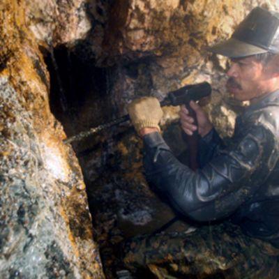 Kaivosmies hakkaa taltalla kultaa irti kaivoksen seinästä.
