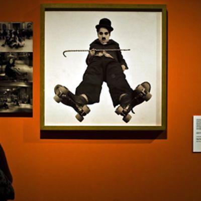 Chaplinin näyttelyssä vieraileva nainen katselee neliömäistä kuvaa Chaplinista punaisella seinällä. Sammakkoperspektiivistä otetussa kuvassa Chaplinilla on knallin ja kävelykepin lisäksi rullaluistimet jaloissaan.