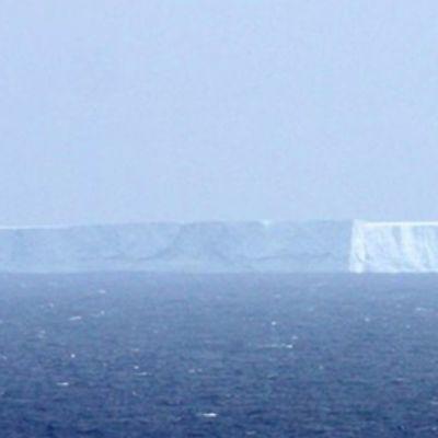 Jättiläismäinen jäävuori ajelehtii avomerellä.