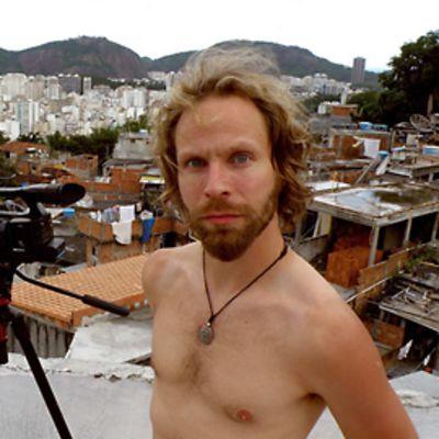 Tuomas Milonoff poseeraa kameralle Brasiliassa videokamera vierellään.