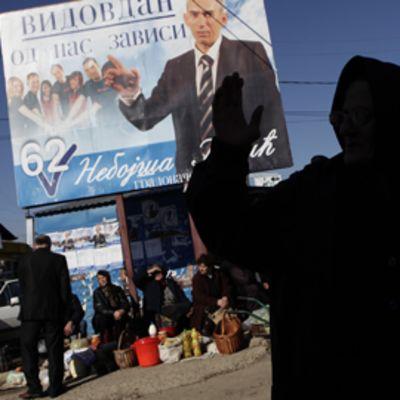 Kosovon serbivähemmistöä suuren vaalijulisteen edessä.