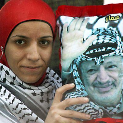 Palestiinalaistyttö pitelee Jasser Arafatin kuvaa