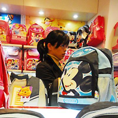 Kiinalainen myyjä Disney-tuotteiden keskellä