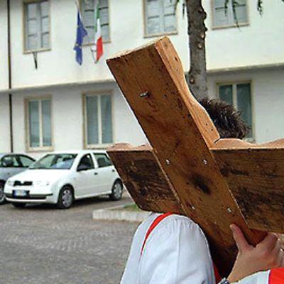 Oppilaat kantavat puista ristiä koulun pihalla