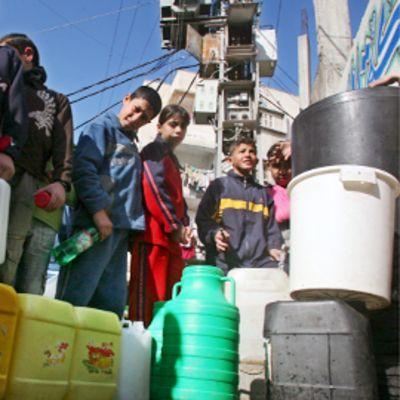 Lapset jonottavat vesikanistereiden kanssa Gazan kaupungissa.