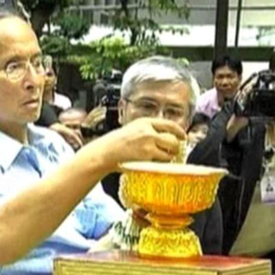 Thaimaan kuningas Bhumibol Adulyadej liikkui pyörätuolilla. Avustajat ja tv-kamerat piirittävät häntä, kun hän on nostamassa kukkaseppelettä kultaisesta maljasta.