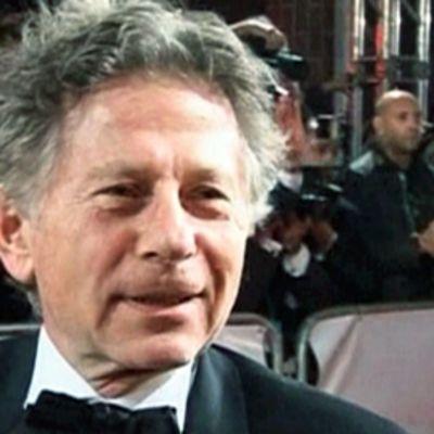 Elokuvaohjaaja Roman Polanski. Taustalla valokuvaajia.