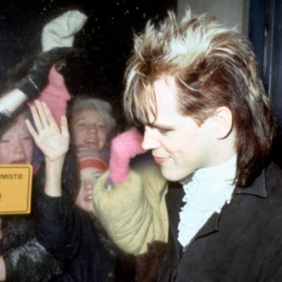 Dingo-yhtyeen laulusolisti Neumann (Pertti Nieminen) nuorten itsenäisyyspäiväjuhlassa 1985. Neumann seisoo ovella, jonka takana huutavia nuoria tyttöjä. Dingon ihailijoita lasioven takana.