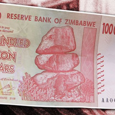 Miehen kädessä on Zimbabwen 100 miljoonan dollarin seteli.