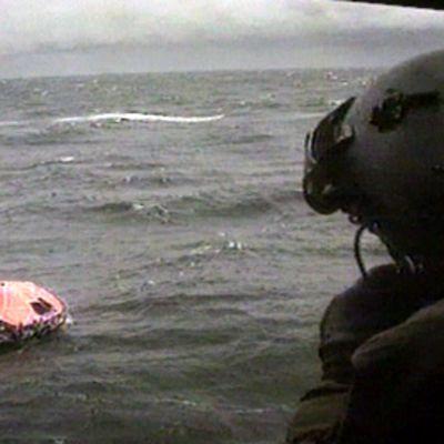 Pelastushelikopterin meripelastaja katsoo meressä kelluvaa Estonian pelastuslauttaa  syyskuussa 1994.