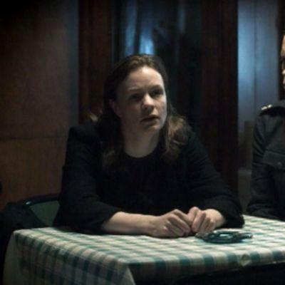 Kerttu Nuortevaa esittävä Minna Haapkylä istuu pöydän ääressä ja tuijottaa eteensä vierellään kuulustelija Paavo Kastaria esittävä Marcus Groth.