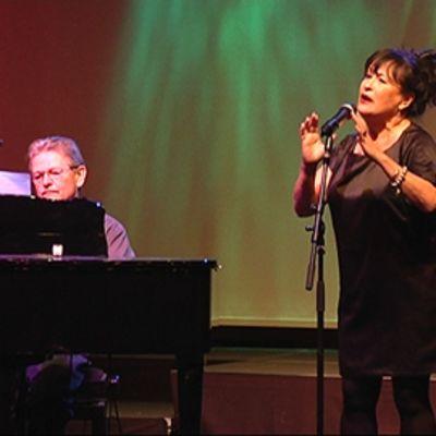 Näyttelijä Sinikka Sokka laulaa teatterin lavalla pianistin säestyksellä.
