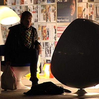 Mies istuu Eero Aarnion suunnitteleman pallotuolin luona messuosastolla. Kuva Habitare 09 -messuilta.