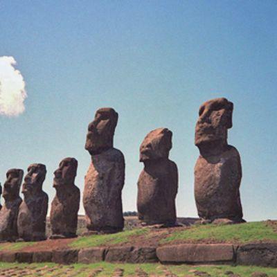 Pääsiäissaarten moai-patsaita rivissä kauniina kesäpäivänä, valkoinen pilvenhattara sinisellä taivaalla.
