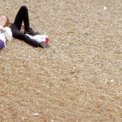 Nainen nojaa miehen vatsaan hietikolla.