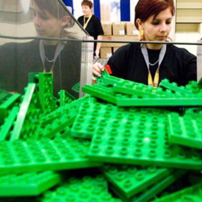 Vihreät leegopalikat etenevät liukuhihnalla työntekijän syliin LEGO:n Budapestin tehtaalla.