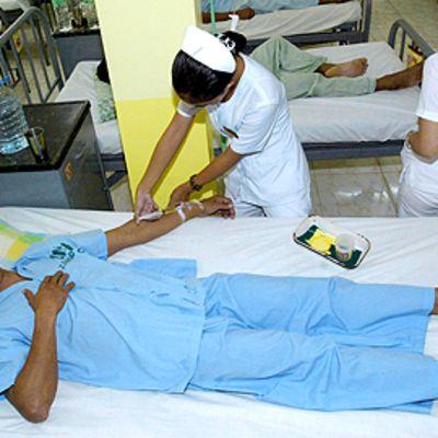 Filippiiniläinen sairaanhoitaja hoitaa tulitaistelussa haavoittunutta sotilasta Zamboanga Cityn sotilassairaalassa 13.8.2009.