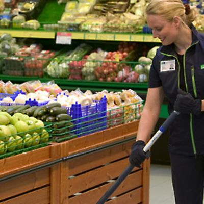 Siivooja moppaa myymälän lattiaa hedelmähyllyjen välissä