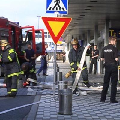 Palomiehiä ja vartijoita lentokentän sisäänkäynnin edessä.