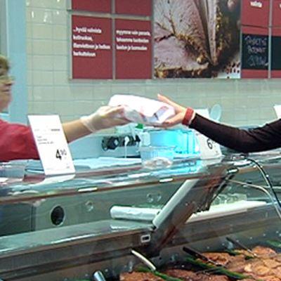 Kauppias ojentaa asiakkaalle paketoidun tuotteen marketin palvelutiskillä.