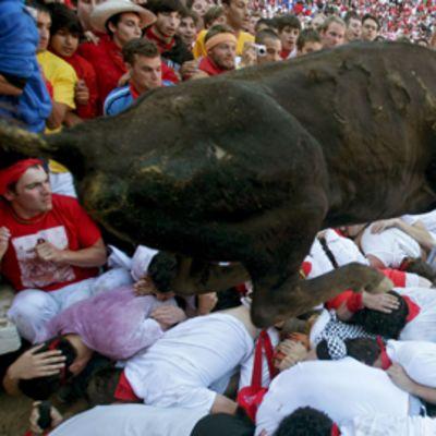 Härkä hyppää juoksijoiden päälle Pamplonan härkäfestivaaleilla.