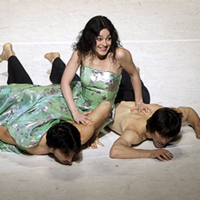 Tanssijat harjoittelevat Pina Bauschin Tanzabend-teosta Saksassa. Kaksi paidatonta miestanssijaa vatsallaan lattialla. Naistanssija istuu heidän päällään mekko yllään.