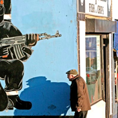 Seinämaalaus jossa kommandopipoinen mies korkeassa polviasennossa rynnäkkökiväärin kanssa.