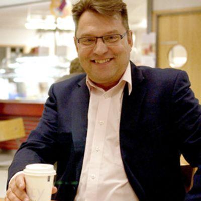 Arto Nurmi hymyilee kahvilla.
