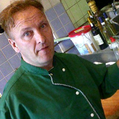 Mieskokki keittiössä lihapalojen äärellä, veitsi kädessään