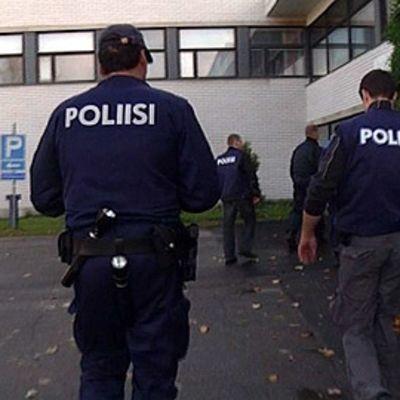 Poliiseja kävelee koulurakennukseen.