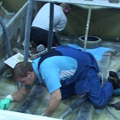 Kuvassa kaksi Nautorin työntekijää työskentelee veneen sisällä.