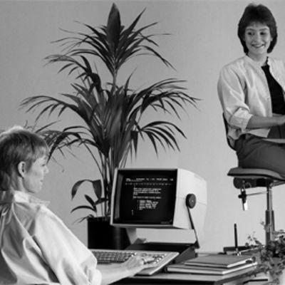 Kaksi konttorityöntekijää vanhojen tietokoneidensa kera.