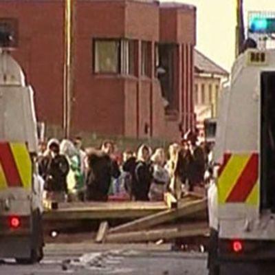 Kaksi poliisiautoa joiden välistä näkyy ihmisiä barrikadin takana.