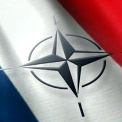 Sotilasliitto Naton logo, taustalla Ranskan lippu, kuvamanipulaatio.