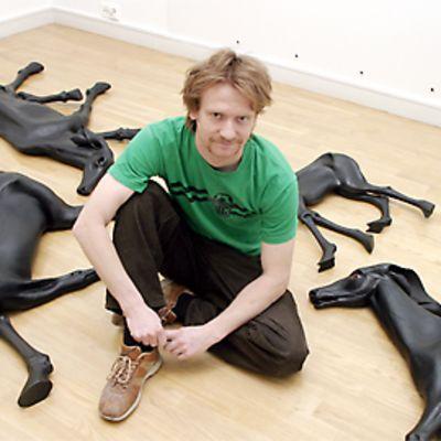Kuvanveistäjä Kim Simonsson istuu lattialla teostensa keskellä.