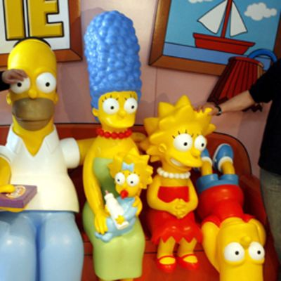 Simpsonit-hahmoja kolmiulotteisina mallihahmoina istumassa sohvalla vierellään Matt Groening ja Al Jean.