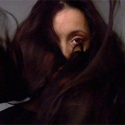 Pitkien tummien hiusten taakse peittyneet naisen kasvot, näkyvissä vain toinen silmä ja otsa