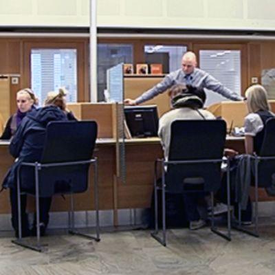 Asiakkaita istumassa pankin konttorissa, virkailijoita tiskin takana.