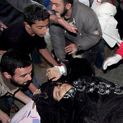 Haavoittunutta palestiinalaisnaista tuodaan sairaalaan