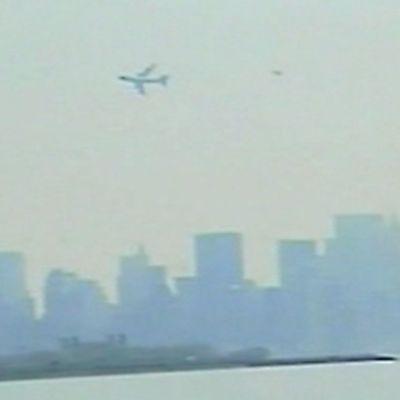 Air Force One ja sitä seuraava hävittäjä New Yorkin silhuetin yllä